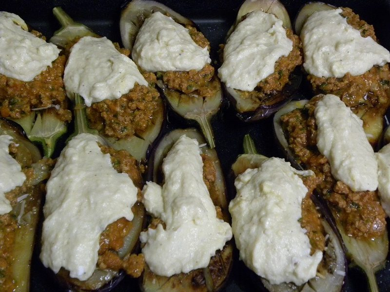 Papoutsakia (stuffed eggplants) with meat sauce and bechamel before baking image