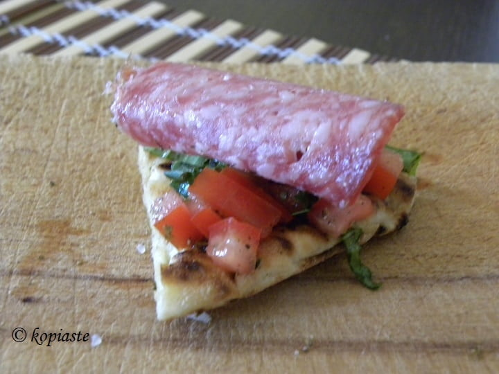 Pita chips with tomato, basil and salami