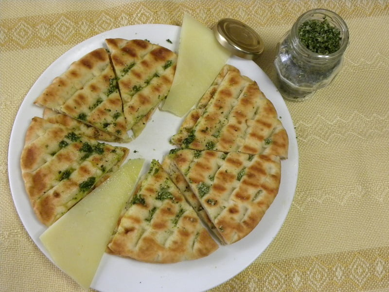 Greek pita chips with olive oil and basil salt image
