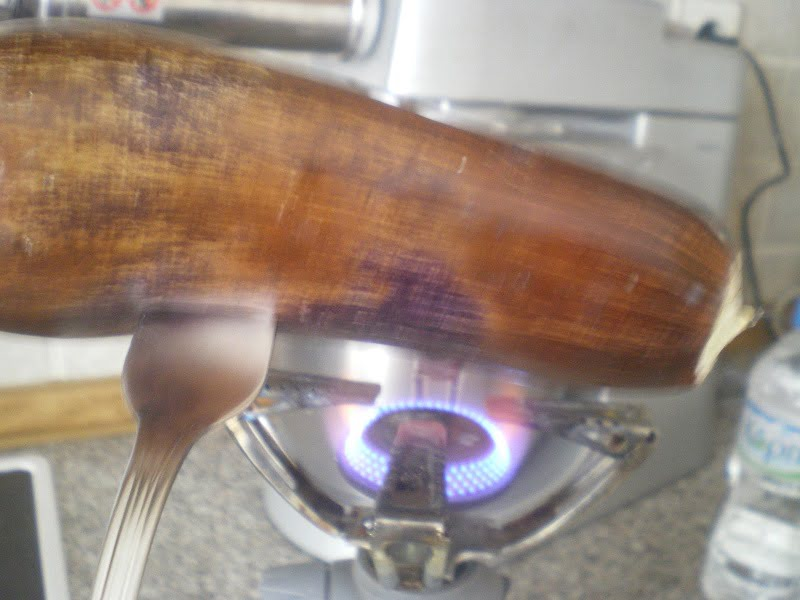 Charring an eggplant over flame image