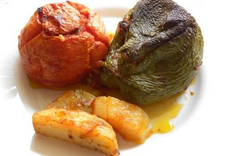 A stuffed tomato and green pepper with potatoes image